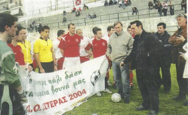 Ο Αλέξης Τσίπρας μιλάει στους ποδοσφαιριστές του Αστέρα 2004 και της Δάφνης Παλαιού Φαλήρου, οι οποίοι κρατούν ένα πανό με μήνυμα: «Να κάνουμε πάλι δάση τα καμένα βουνά μας»
