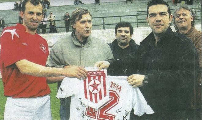 Στην Καισαριανή βρέθηκε το μεσημέρι του Σαββάτου ο Αλέξης Τσίπρας. Ο πρόεδρος του ΣΥΡΙΖΑ χαρακτήρισε «καρδιά του αθλητισμού» το ερασιτεχνικό ποδόσφαιρο και έδειξε ιδιαίτερο ενδιαφέρον για τις οικολογικές ευαισθησίες του Αστέρα 2004. Στη φωτογραφία, ο Αλέξης Τσίπρας με τον πρόεδρο της ομάδας Νίκο Μάλλιαρη και τον αρχηγό Γιώργο Αναστασάκη λαμβάνει τη φανέλα και το λάβαρο του Αστέρα