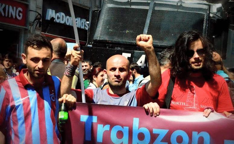 Στο κέντρο της φωτογραφίας ο Κοράι Τσαπόγλου, με υποστηρικτές της ομάδας Τράμπζονσπορ σε παλιότερη διαδήλωση στην Τραπεζούντα εναντίον του καθεστώτος της Άγκυρας. Πέρυσι τον Ιούλιο έπεσε μάρτυρας στο Σουρούτς, όπου είχε πάει για να συμπαρασταθεί στους Κούρδους, ανεμίζοντας τη σημαία της ομάδας του… και μετατράπηκε σε σύμβολο για τους συντοπίτες του.