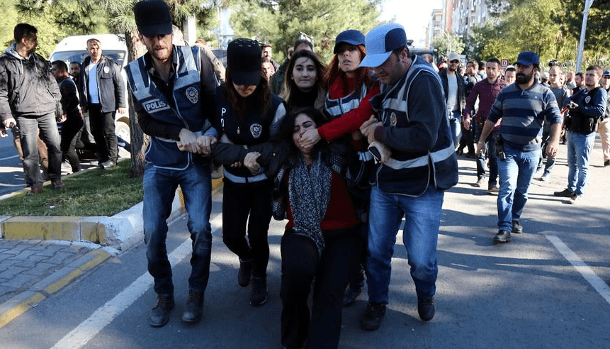 Η στιγμή της βίαιης σύλληψης από ασφαλίτες της Σεμπαχάτ Τουντσέλ, συμπροέδρου του κουρδικού κόμματος DBP, που αποτελεί συνιστώσα του Δημοκρατικού Κόμματος των Λαών (HDP). Λίγο πριν τη σύλληψή της δήλωνε: «Το πιθανότερο είναι ότι θα με συλλάβουν. Αυτό δεν μπορεί να μας φοβίσει. Θα συνεχίσουμε την αντίσταση ό,τι κι αν γίνει. Και θα νικήσουμε!». Οι ασφαλίτες προσπαθούν να της κλείσουν το στόμα, καθώς συνέχισε να φωνάζει συνθήματα για να δώσει κουράγιο στους συντρόφους της…