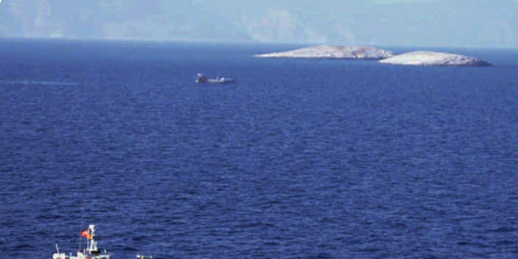 A Turkish coast guard boat, foreground, faces off a Greek coast guard ship near the controversial Kardak (Imia) islets, visible in the background, on Monday, Jan. 29, 1996. The claims of sovereignty by Greece and Turkey on the uninhabited islets reached a dangerous level Monday when Greek Premier Costas Simitis warned Turkey with a threat of military action. In the background also visible is the Turkish coast, which is 3.8 miles from the islets. (AP Photo/Hurriyet)