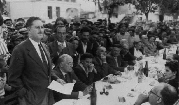 Ο Πολ Πόρτερ (όρθιος αριστερά) στις 10 Οκτωβρίου του 1949 απευθύνεται στις τοπικές Αρχές και στους κατοίκους της αγροτικής περιοχής Ανθήλη στα περίχωρα της Λαμίας. Ολοι έχουν συγκεντρωθεί για γεύμα στην πλατεία γιορτάζοντας την πρώτη συγκομιδή ρυζιού το οποίο καλλιεργήθηκε με τη βοήθεια αμερικανών ειδικών που μελέτησαν τα νερά του Σπερχειού. Δίπλα στον Πόρτερ διακρίνονται ο υπουργός Ναυτικών Γεράσιμος Βασιλειάδης, η κ. Πόρτερ, ο υπουργός Γεωργίας Χρήστος Γουλόπουλος και ο αναπληρωτής επικεφαλής της αμερικανικής αποστολής βοήθειας Τζον Μπλάντφορντ