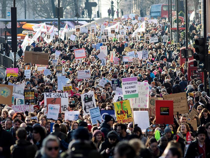 Με φόντο την εκκίνηση της επίσημης διαδικασίας για το Brexit και την ανάληψη της προεδρίας από τον Τραμπ, η Πορεία των Γυναικών στο Λονδίνο κατέβασε πολύ κόσμο στο δρόμο το περασμένο Σάββατο. Ήταν μια διαδήλωση 100.000 ανθρώπων με πλακάτ εστιασμένα σε έμφυλα θέματα, κυριαρχία απλού, «χύμα» κόσμου και όχι οργανωμένων μπλοκ (παρότι κι αυτά υπήρχαν), με πολλά χρώματα και απουσία συνθημάτων, μα γρήγορη μετάδοση εμψυχωτικών επιφωνημάτων που τα αντικαθιστούσαν. Αρκετά διαφορετικό από ό,τι έχουμε συνηθίσει στην Ελλάδα, μα και με κάποιες ομοιότητες. Η αμηχανία, η απουσία συνθημάτων και η αίσθηση της πολιτικής σούπας που, μη ενοποιημένη ακόμα, αποτελείται από τα μέρη της χωρίς να έχει συντεθεί σε σύνολο, θύμιζαν αρκετά τις πρώτες συγκεντρώσεις των πλατειών… [φωτό: Dan Kitwood/Getty Images]